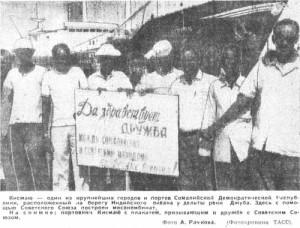 На снимке: портовики Кисмаю с плакатом, призывающим к дружбе с Советским Союзом.
